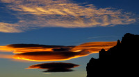 Lenticular clouds floating over rock formations